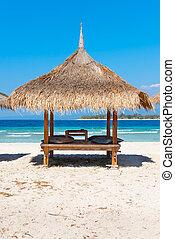 Beach house on the sandy coast of blue sea - Beach house on...