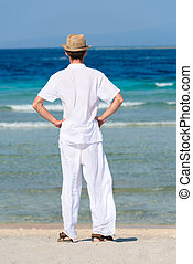 Man in white suit on a tropical beach, back view - Back view...