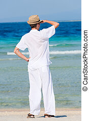 Man in a white suit against the sea - Back view a man with...