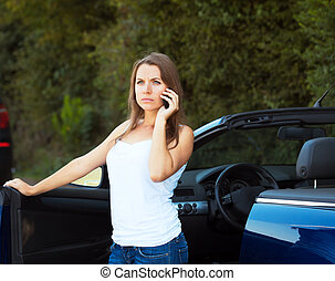 Caucasian girl on a cell phone service or tow truck traffic...