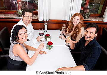 smiling happy people in restaurant drinking talking having...