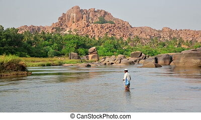Man wading in mountain river - Local man bathing in mountain...