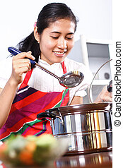 Asian woman tasting her cooking