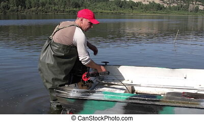 Fisherman - man installs a boat outboard motor