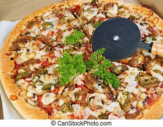 Large Pizza with cutter on top - Photo of fresh pizza topped...