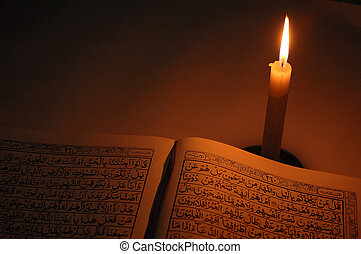 holly quran with single candle light in dark room