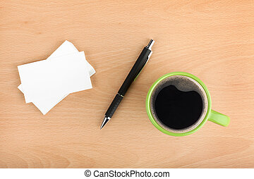 Blank business cards with pen and coffee cup on wooden...