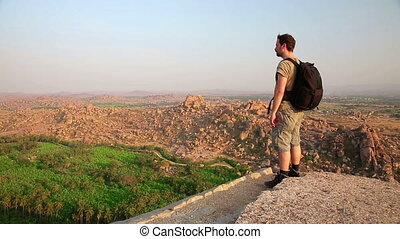 Man looking at mountain landscape - Male tourist admiring...