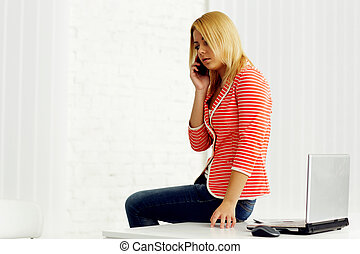 Young beautiful woman sitting on the table and speaking on...