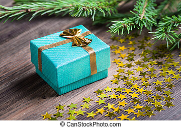 Christmas gift with stars and fir tree twig on wooden table...