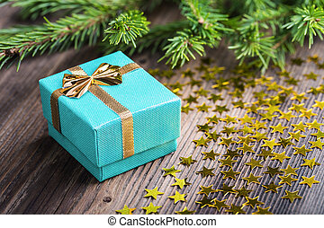Christmas gift with stars and fir tree twig on wooden table
