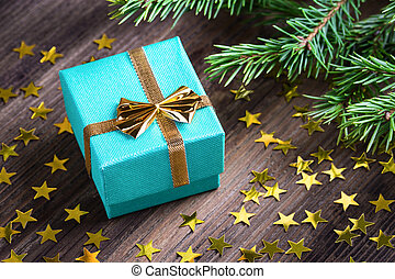 Christmas gift with stars and fir branch twig on wooden...