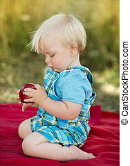 Cute boy - Cute kid holding a red apple in green park