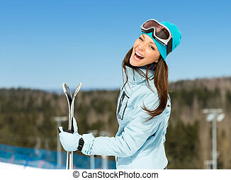 Half-length portrait of female downhill skier with skis in...