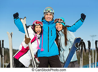 Half-length portrait of group of skier friends with hands up...