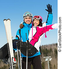 Male skier holds woman in his arms - Male skier holds woman...