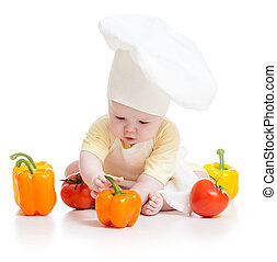 baby wearing a chef hat with healthy  food vegetables