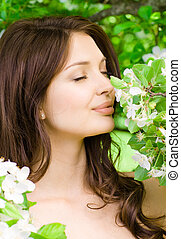Young woman smells the blossomed tree - Portrait of young...