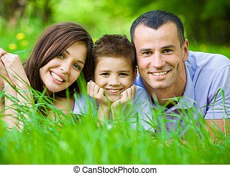 Happy family of three lying on grass. Concept of happy...