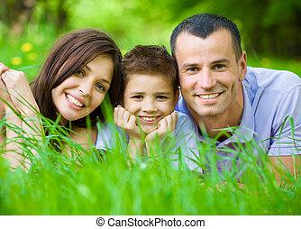 feliz, familia, tres, acostado, pasto o césped