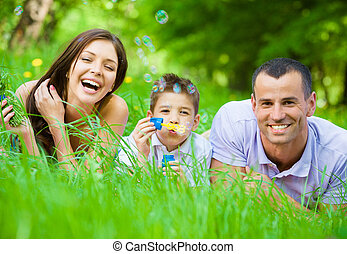 Family of three lying on grass and blows bubbles - Happy...