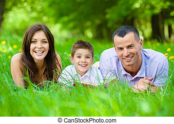 Happy family of three lying on grass with book - Happy...
