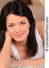 Just doing nothing. Close-up of beautiful young woman lying on the floor at her room and looking at camera