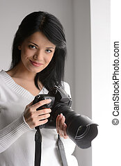 Young woman with camera. Portrait of beautiful young woman holding a camera and looking at you