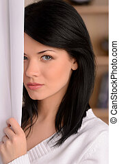 Mysterious girl. Portrait of beautiful young woman hiding...