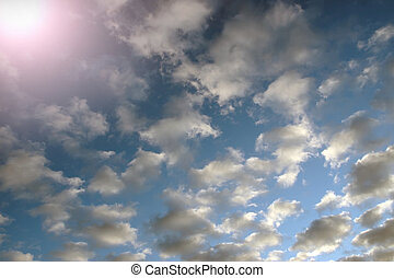 blue skys - rays of sunshine against a cloudy blue sky
