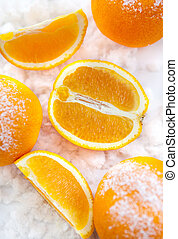 Oranges on the snow - Oranges and slices of orange on the...
