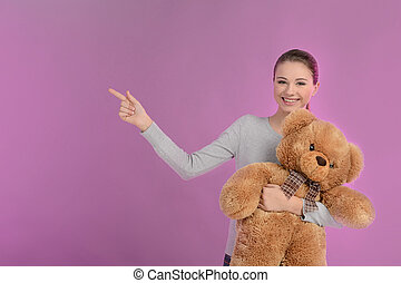 Teenage girl pointing. Happy teenage girl holding a teddy...
