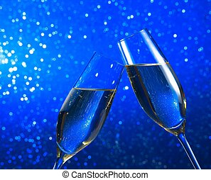 champagne flutes on blue light bokeh background - champagne...