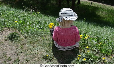 girl pick flower - girl child sit on ground and pick up...