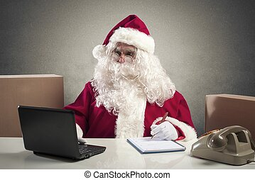 Santa Claus office - Santa Claus working with laptop in a...
