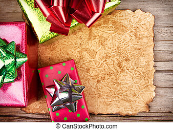 torn paper on wooden background with Christmas presents -...