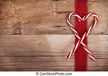 Candy canes and ribbon on wooden background - Candy canes...