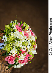 Beautiful bridal bouquet with golden rings in basket