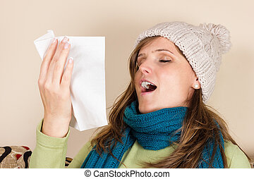 Young woman sneezing in a tissue in the living room,