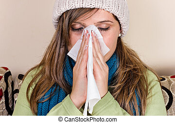 Young woman blowing her nose into tissue
