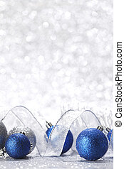 Christmas balls and ribbons decoration on shiny silver...