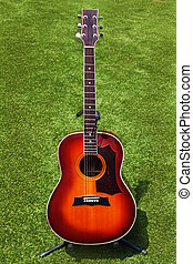Acoustic guitar on background of green grass