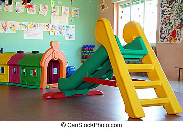 slide and plastic tunnel in the playroom of a preschool -...