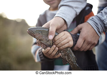 Fishery - Hands of mother and son holding trapped fish