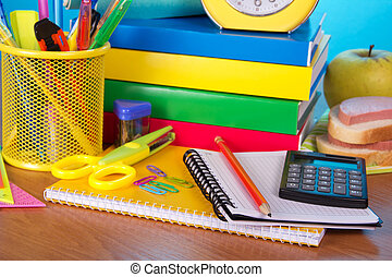 Table piled high with school supplies - Pile of books, an...