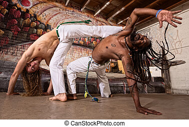 Capoeira Kicking - Pair of capoeira performers doing a...