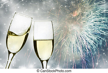 Glasses with champagne against fireworks and clock close to...