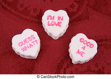 Conversational candy hearts over red fabric