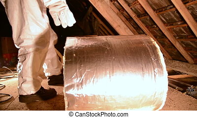 insulation - a man rolling out insulation mineral wool.