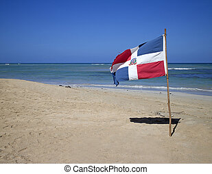 dominican republic flag planted in the sand of punta cana...